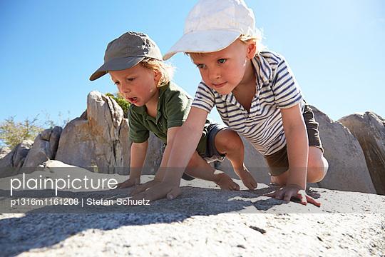 Zwei Jungen krabbeln über Felsen, Kubu Island, Makgadikgadi Pans Nationalpark, Botswana - p1316m1161208 von Stefan Schuetz