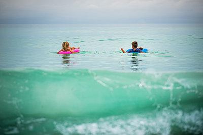 Siblings in inflatable rings floating on sea - p1166m1489108 by Cavan Images