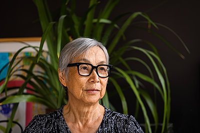 Portrait of Senior Woman wearing glasses at home with plants - p1166m2285616 by Cavan Images