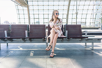 Woman sitting at chair in train station and talking on the phone - p1332m2045754 by Tamboly
