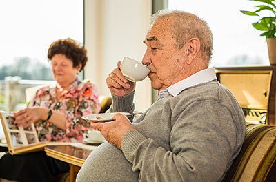 Senior man drinking coffee at home - p300m1018951f by Uwe Umstätter