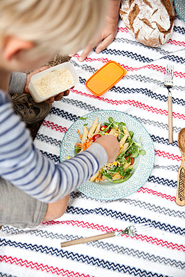 Boy dispersing grated cheese on pasta salad during a picnic in forest - p300m1499234 by Michelle Fraikin