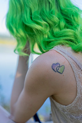 Tattoo on shoulder of young woman with dyed green hair - p300m2024159 by VITTA GALLERY