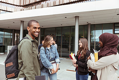 Portrait of smiling man standing with female friends talking at campus in university - p426m2072233 by Kentaroo Tryman