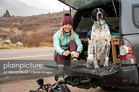 Portrait of smiling young woman tying shoelace while sitting with dog in trunk of off-road vehicle during winter - p1166m2258432 by Cavan Images