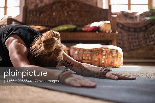 Tattooed female stretching in Utthita Balasana pose - p1166m2285644 by Cavan Images