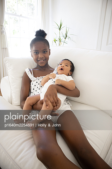 Dark-skinned girl with baby on the sofa - p1640m2254591 by Holly & John