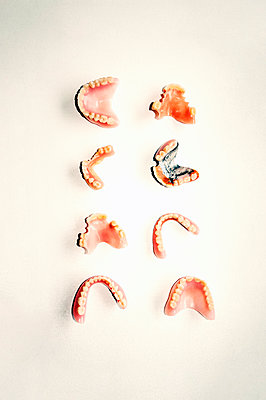 Eight used false teeth parts on white background - p1047m2233827 by Sally Mundy