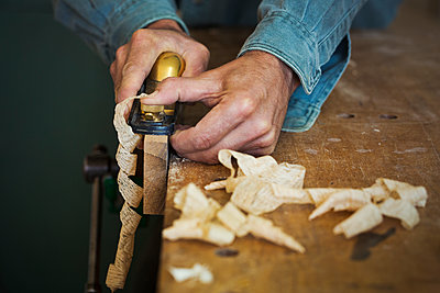 A craftsman holding a spokeshave and using it to shape a piece of wood in a clamp.  - p1100m1522483 by Mint Images