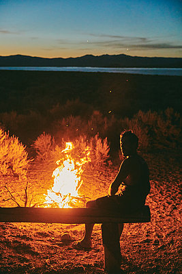 Young man by campfire in Mono Lake at night in northern California. - p1166m2202113 by Cavan Images