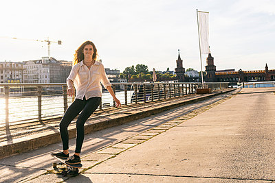 Young woman skateboarding on bridge, river and buildings in background, Berlin, Germany - p429m2077805 by Tamboly