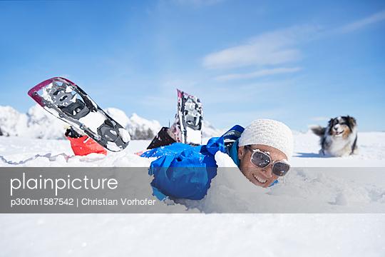 Austria, Tyrol, snowshoe hiker and dog, having fun in the snow - p300m1587542 von Christian Vorhofer