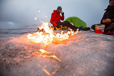 Campfire moves across the glacier as two men camp on a glacier. - p1166m2189698 by Cavan Images