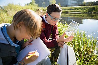 Students examining water and taking notes field trip - p1192m1078415f by Hero Images