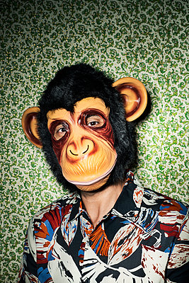 Man with a monkey mask against a wallpapered wall - p1423m2116067 by JUAN MOYANO