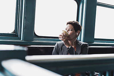 Businesswoman on a ferry drinking coffee - p300m2013067 by Uwe Umstätter