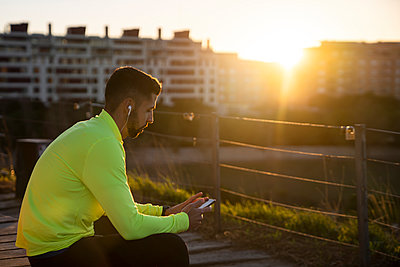 Male sportsperson listening music while sitting at park during sunset - p300m2250384 by Albert Martínez