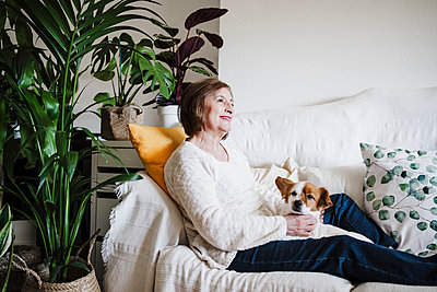 Smiling woman with Jack Russell Terrier looking away while sitting on sofa at home - p300m2264962 by Eva Blanco