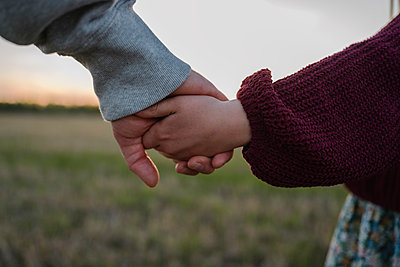 Daughter and father holding hands in field during sunset - p300m2281796 by Ekaterina Yakunina