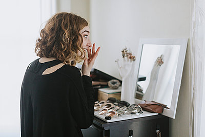 Woman at dressing table applying make up - p429m1569676 by Lena Mirisola