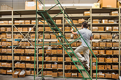 Mixed race worker examining boxes in textile factory - p555m1453326 by Erik Isakson