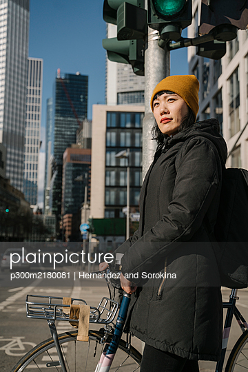 Woman with bicycle in the city, Frankfurt, Germany - p300m2180081 by Hernandez and Sorokina