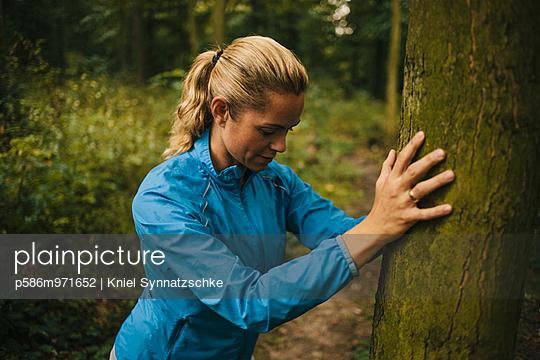 Junge Frau macht eine Dehnübung im Wald - p586m971652 von Kniel Synnatzschke