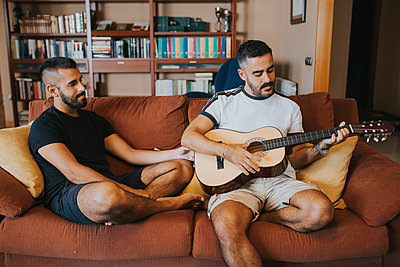 boy plays guitar sitting on the couch his boyfriend - p1166m2193911 by Cavan Images
