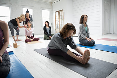 Woman practicing yoga forward bend in yoga class - p1192m1583311 by Hero Images