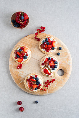 Pies with different berries on wooden board - p300m1047623f by Mandy Reschke