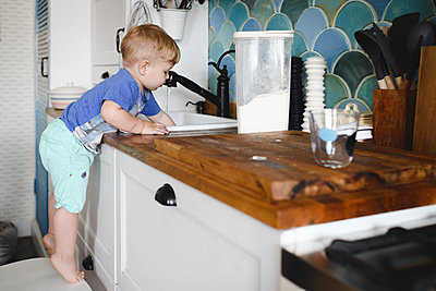 Little boy standing on tiptoes on chair in kitchen washing dishes - p300m2119609 by Ekaterina Yakunina