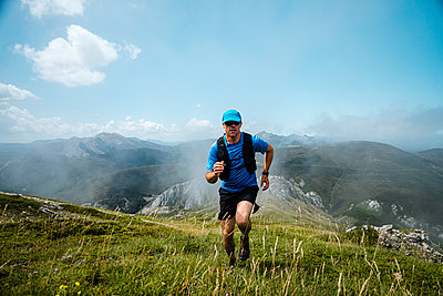 Mature sportsman trail running in the mountains on meadow against blue sky - p300m2243662 by Manu Prats