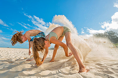 Australia, New South Wales, Pottsville, boy and girl digging in sand on beach - p300m950720f by Holger Spiering