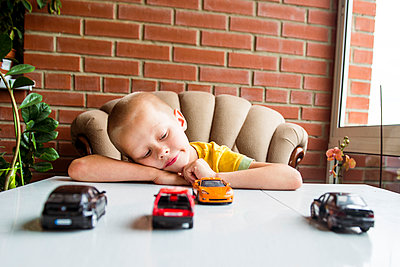 Caucasian boy playing with toy cars at desk - p555m1411164 by Aleksander Rubtsov