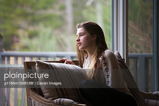 Teenage girl looking away while sitting on sofa at home - p1166m1099138f by Cavan Images