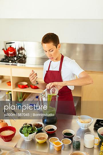 Woman preparing a smoothie in kitchen - p300m1587045 von Bonninstudio