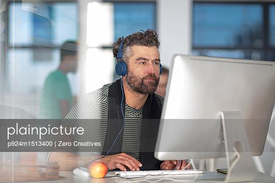 plainpicture | Photo library for authentic images - plainpicture p924m1513400 - Man in office wearing headp... - plainpicture/Image Source/Zero Creatives