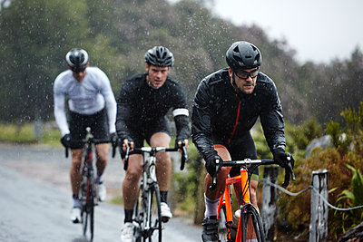 Dedicated male cyclists cycling on rainy road - p1023m1584008 by Richard Johnson