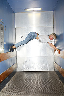 Elevator acrobatics - p276m2115674 by plainpicture