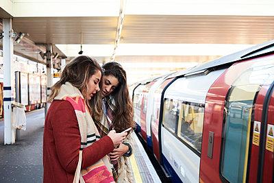 UK, London, two women using cell phone at underground station platform - p300m2103809 von Ivan Gener