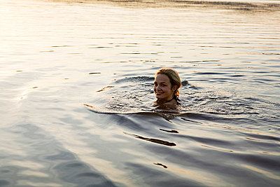 Woman swimming in a lake - p4240267 by Justin Winz