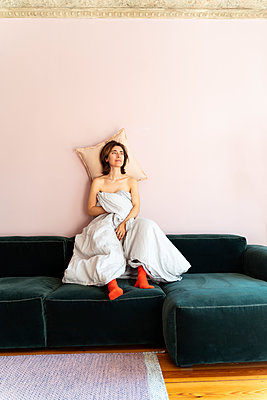 Frau sitzt mit Bettdecke auf dem Sofa - p432m2168902 von mia takahara