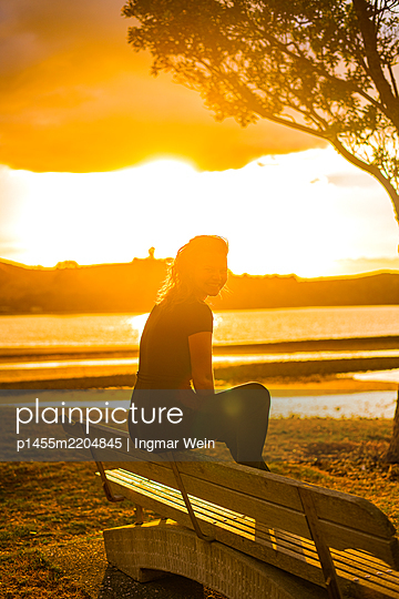 Woman on park bench at sunset - p1455m2204845 by Ingmar Wein