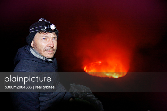 Africa, Democratic Republic of Congo, Virunga National Park, Man sittiing over Nyiragongo volcano crater - p300m2004586 von realitybites