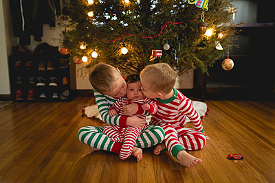 Brothers kissing sister while sitting against Christmas tree at home - p1166m1229498 by Cavan Images