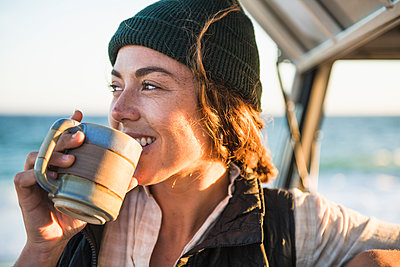 Young woman enjoying drink in mug while beach car camping alone - p1166m2285577 by Cavan Images