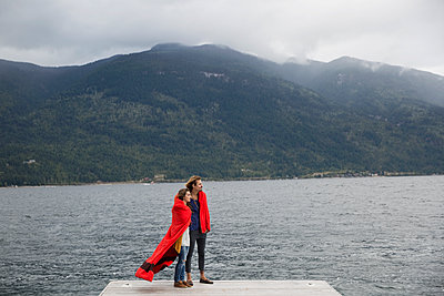 Couple wrapped in blanket on lake dock - p1192m1078281f by Hero Images