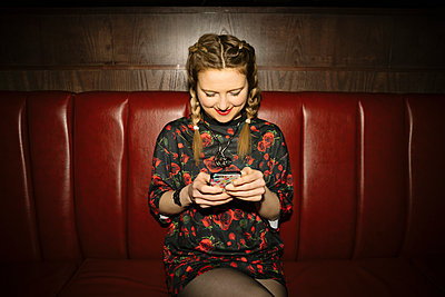 Female millennial texting with smart phone in nightclub - p1192m1583674 by Hero Images