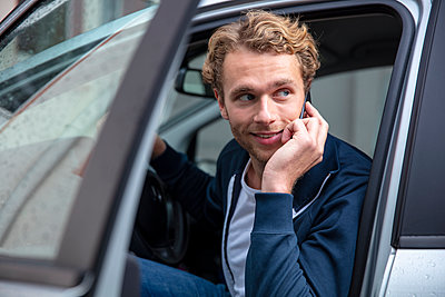 Young man phoning and sitting in car, looking sideways - p300m2155623 by Robijn Page