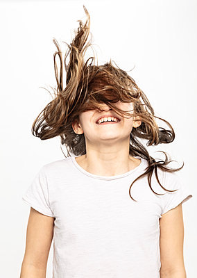 Happy girl with flying hair, white background - p429m2145804 by Matelly